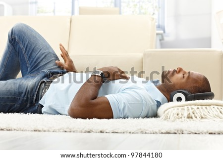 Leisure with music, ethnic man lying on living room floor with headset, enjoying with closed eyes.