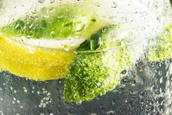 Lemon and basil thrown into the water. Cold drink on hot days