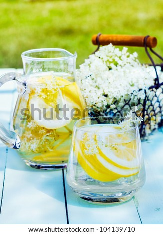 Lemon and cedar refreshment. Flowering Cedar Lemonade with water and citrus slices outdoors on a wooden table. A basket with blooming cedar in the background - stock photo