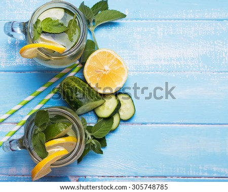 Lemon and cucumber detox water in glass jars on blue colored wooden background, top view