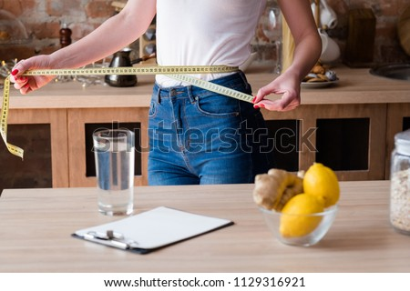 lemon and ginger detox diet for weight loss. slim and fit body. woman measuring her waist with a tape #1129316921