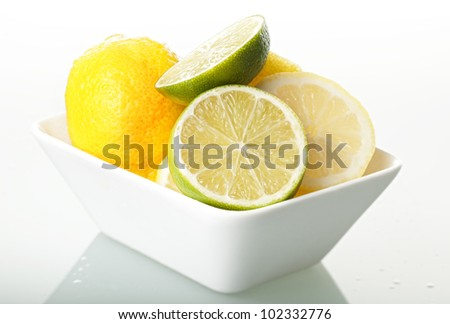 lemon and lime in white bowl - stock photo