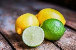 Lemon and limes on rustic wood
