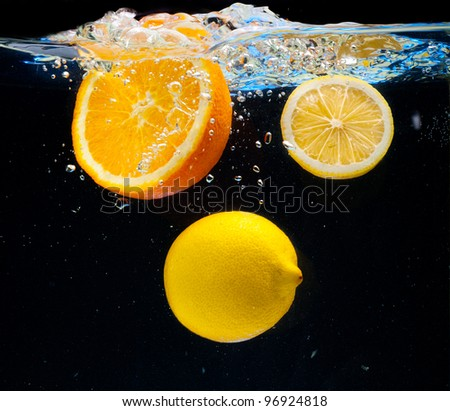 Lemon and orange floating in the water on a black background
