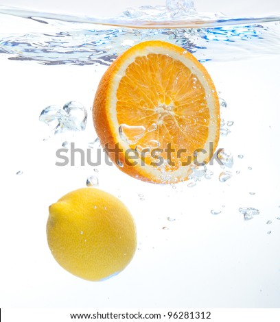 Lemon and orange floating in the water on a white background - stock photo