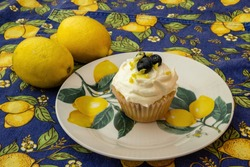 Lemon blueberry cupcake with blueberries and lemon zest with lemons and decorative lemon plate and tablecloth.