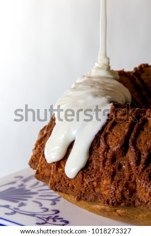 Lemon Bundt Cake Being Drizzled with Cream Cheese Icing