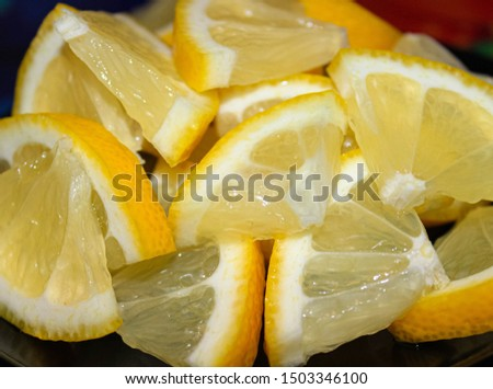 Lemon, cut into quarters and piled in a pile, close-up.