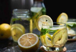 Lemon detox infused water in clear glass on dark background.  Drinking organic lemon detox infused water for toxin cleansing is healthy. Detox infused water can boost vitamin and digestive system.