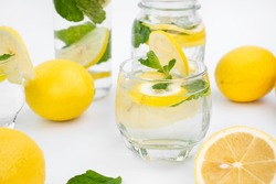 Lemon detox infused water in clear glass on white background.  Drinking organic lemon detox infused water for toxin cleansing is healthy. Detox infused water can boost vitamin and digestive system.
