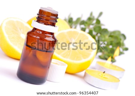 Lemon essential oil, fresh lemon and candles, isolated on white