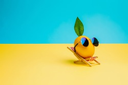 Lemon fruit chilling in beach chair on the blue and yellow background. Summer vacation concept. Sunglasses on lemon with green leaf relaxing on the sunbed. Creative art minimal aesthetic.