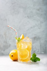 Lemon ice tea on concrete gray background with mint and ice, nice drink for summer hot season, vertical orientation