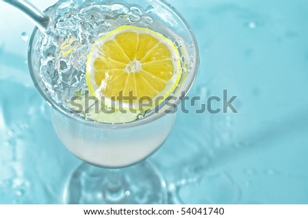 Lemon in glass water with bubbles