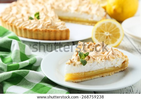 Lemon meringue pie on plate on white wooden background