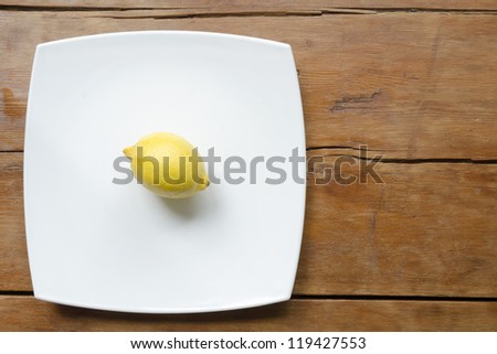 lemon on white ceramic square dish on the vintage wooden table