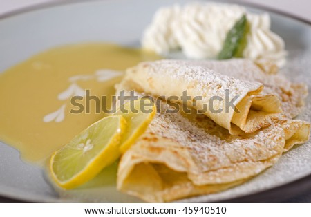 Lemon pancakes/crepes with sauce and cream