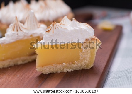 Lemon Pie portions meringue toasted on wooden board on kitchen rag Foto d'archivio ©