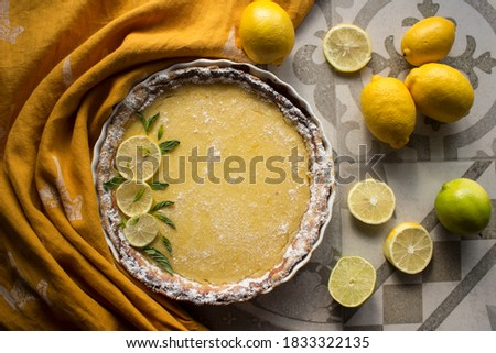 Lemon pie top view photo. Fresh baked tart decorated with lime slices and mint. Grey tiled kitchen table, yellow fabric texture, fresh fruits close up.  Foto stock ©