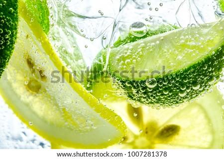 Lemon slice drop in fizzy sparkling water, juice refreshment