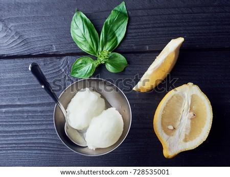 Shutterstock lemon sorbet ice cream in a silver bowl with basil leaf and lemon wedges. top view