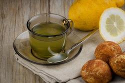 Lemon tea and cookies on wooden table.