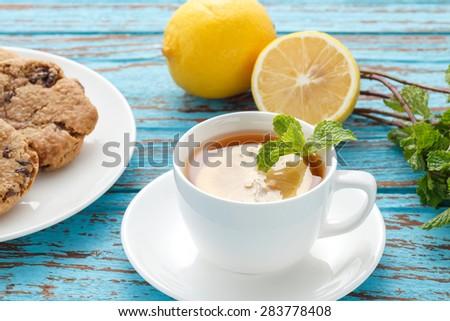 lemon tea mint fresh drink raisin cookies summer refreshment still life blue background wood teak