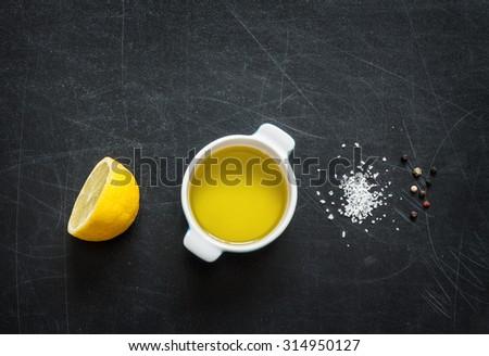 Lemon vinaigrette dressing ingredients on black chalkboard background from above. Lemon, olive oil, salt and pepper. Layout with free text space.