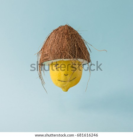 Lemon with coconut hat on pastel blue background. Funny food creative concept.