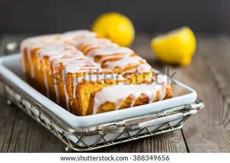 Lemon yogurt loaf cake, sliced on a creative plate on wooden background for your design