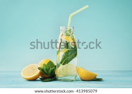Lemonade drink of soda water, lemon and mint leaves in jar on turquoise background.