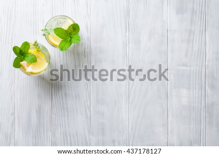 Lemonade glasses with lemon, mint and ice on wooden table. Top view with copy space