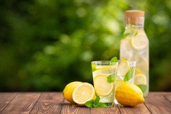 lemonade in glass and bottle on wooden table outdoors. Summer refreshing drink. Cold detox water with lemon