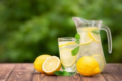 lemonade in glass and jug on wooden table outdoors. Summer refreshing drink. Cold detox water with lemon