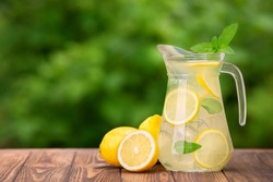 lemonade in glass jug on wooden table outdoors. Summer refreshing drink. Cold detox water with lemon