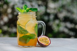 Lemonade or tropical cocktail with lemon, passion fruit, orange and mint, cold refreshing drink or beverage with ice on white table.