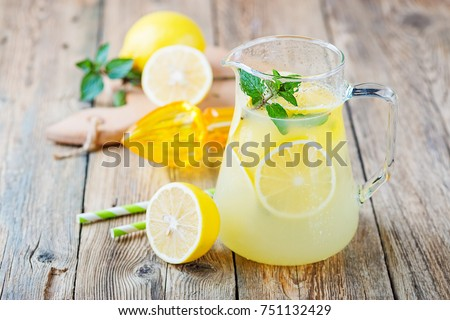 Lemonade pitcher with lemon, mint and ice on table.