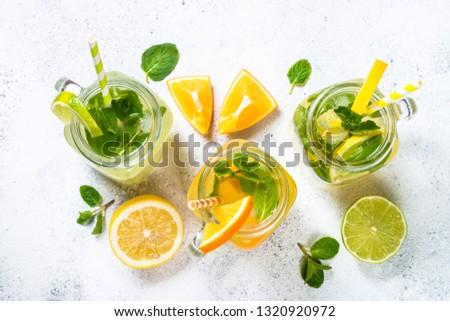 Lemonade set. Lemonade, mojito and orange lemonade. Iced summer drink in mason jar with ingredients on white table top view.
