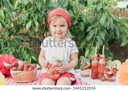 Lemonade Stand. Adorable little girl trying to sell lemonade. strawberry lemonade with ice and mint as summer refreshing drink in jars. Cold soft drinks with fruit. Child drinking lemonade in jar