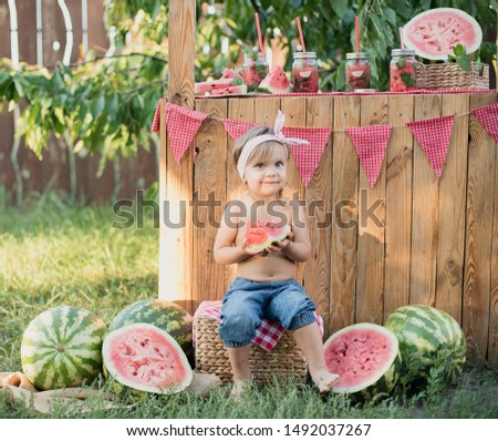 Lemonade Stand. Adorable little girl trying to sell lemonade. Watermelon lemonade with ice and mint as summer refreshing drink in jars. Cold soft drinks with fruit. Child drinking lemonade in jar