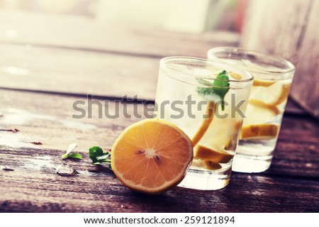 Lemonade with fresh lemon on wooden background #259121894