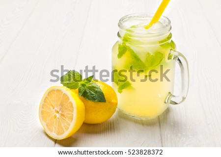 Lemonade with ice in fancy glass with straw, there are lemons and a half near glass.