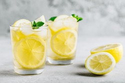 Lemonade with lemon, mint and ice cubes in glass on gray stone background. Cold summer refreshing drink or beverage