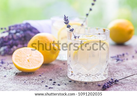 Lemonade with lemons and lavender on stone table over nature background