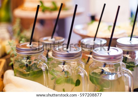 Lemonade with mint in glass cup with straws in area of wedding party
