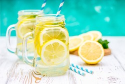 Lemone water. Banks with handles with cold lemonade water on a white wooden background. Lemons. Sweet soft drink on lemon juice with water.