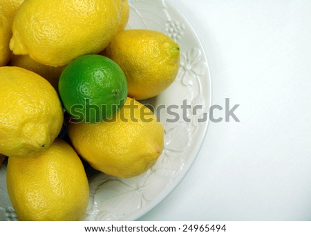 Lemons and Lime with white embossed plate on white table cloth