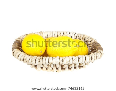 Lemons in a woven basket isolated over white background