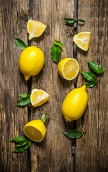 Lemons sliced and whole with leaves. On wooden background.  Top view