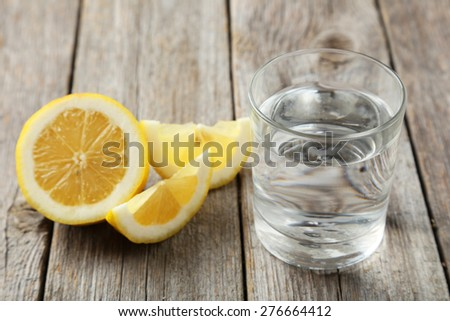 Lemons with glass of water on grey wooden background